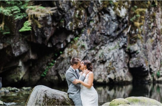 Bride and Groom embracing each other and kissing while standing at the bottom of a ravine