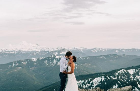 Bride and group on top of mountain holding and kissing each other on their wedding day