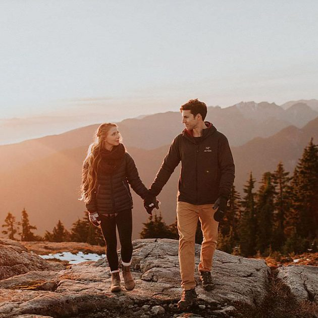 Couple holding hands and looking at each other intently on top of Mount Seymour in North Vancouver, British Columbia