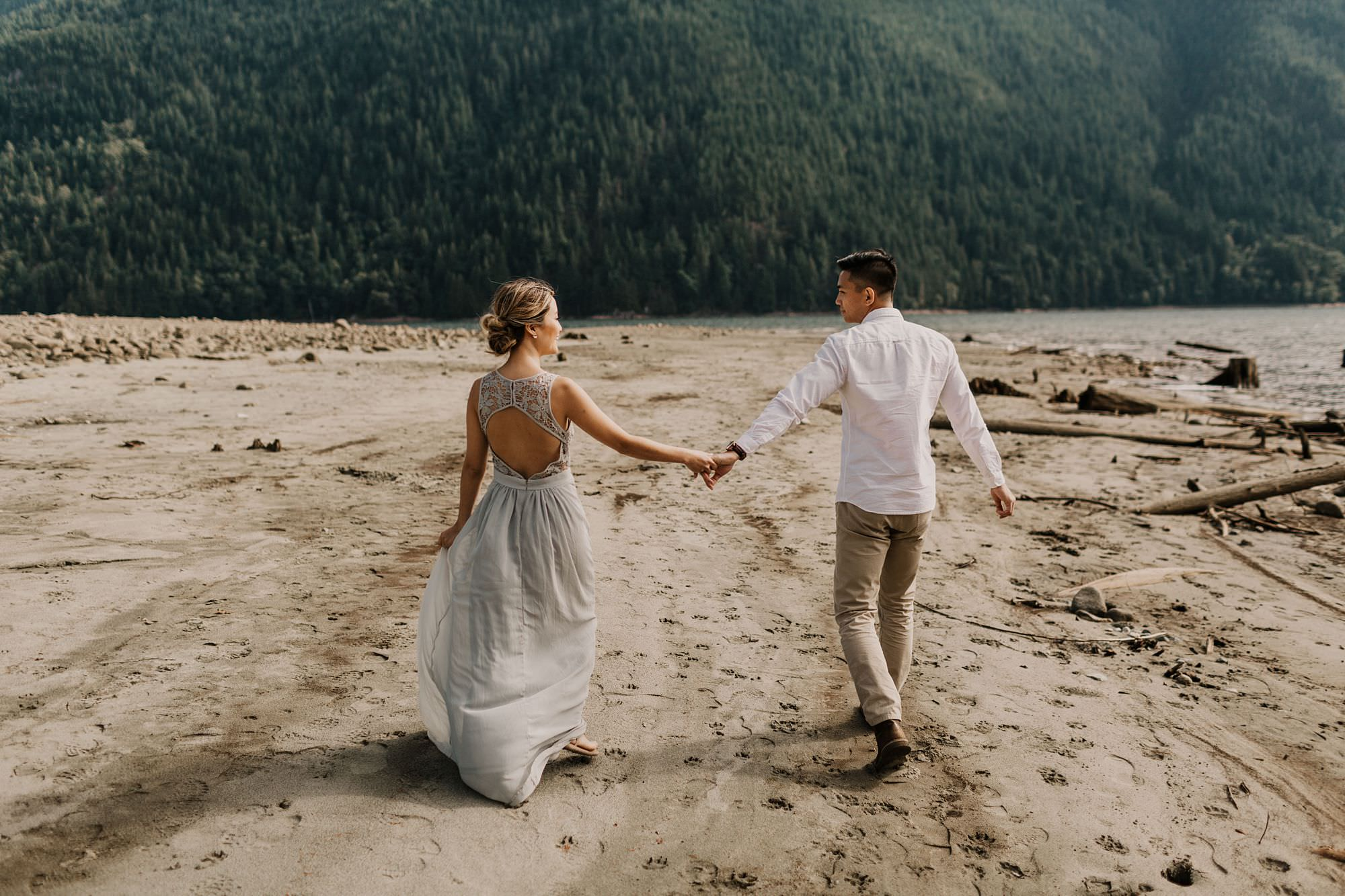 Asian couple holding hands and walking along North Beach in Golden Ears Park, British Columbia