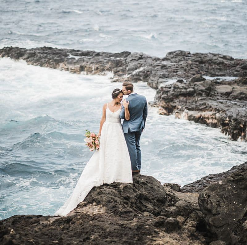 Bride and Groom standing on the side of a cliff overlooking the blue ocean at Olivine Pools in Maui, Hawaii