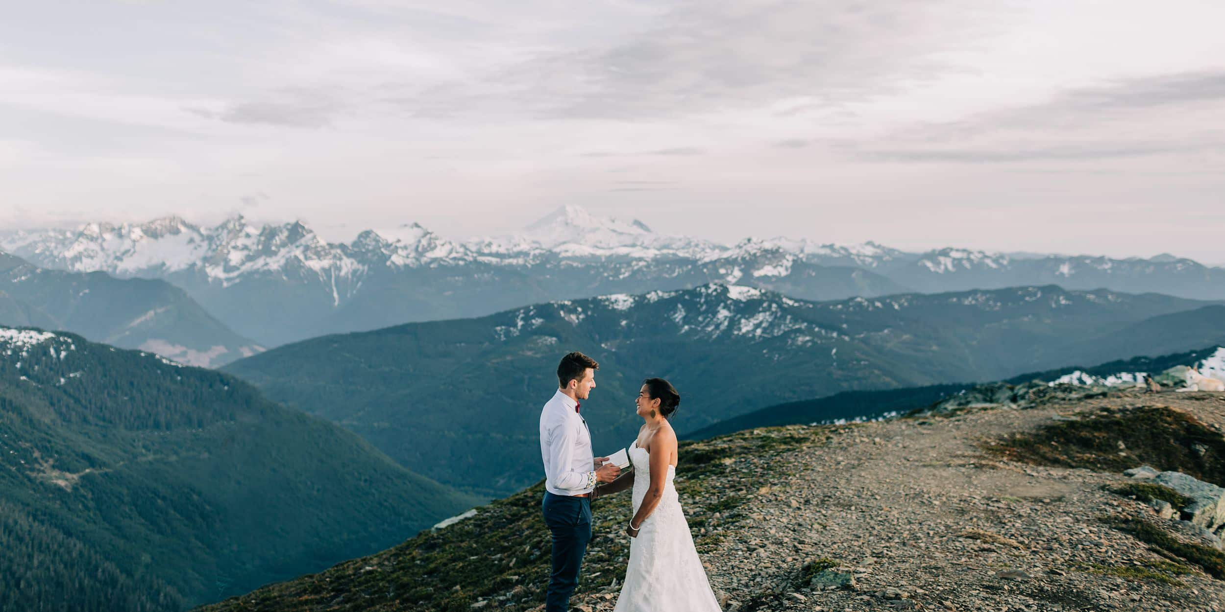 Vancouver wedding videographer - Couple standing on top of mountain reading wedding vows to each other