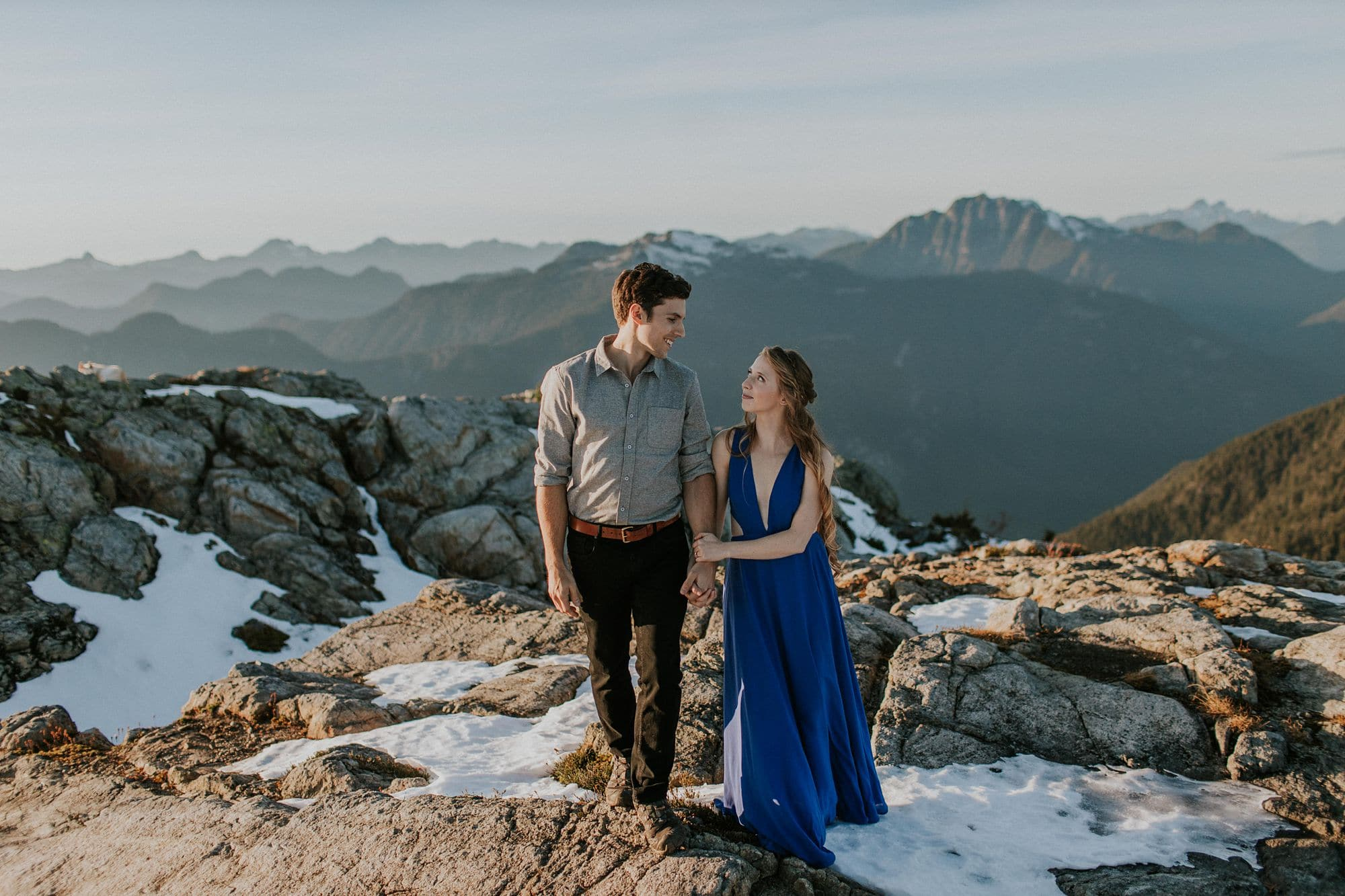 couple standing in pile of snow on top of mount seymour. blue dress