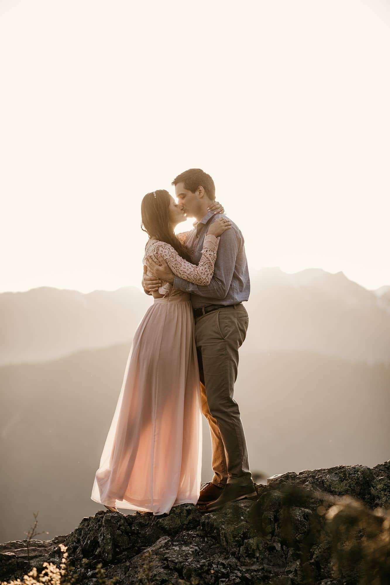Dog Mountain engagement. Couple kissing with sunsetting behind mountain peaks
