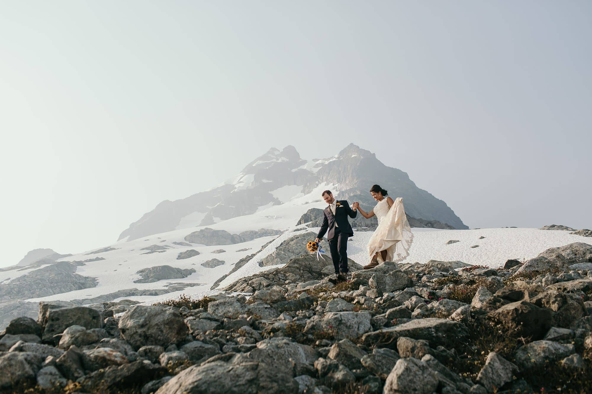 vancouver wedding photography - bride and groom walking down talus and scree on top of Mount Tantalus
