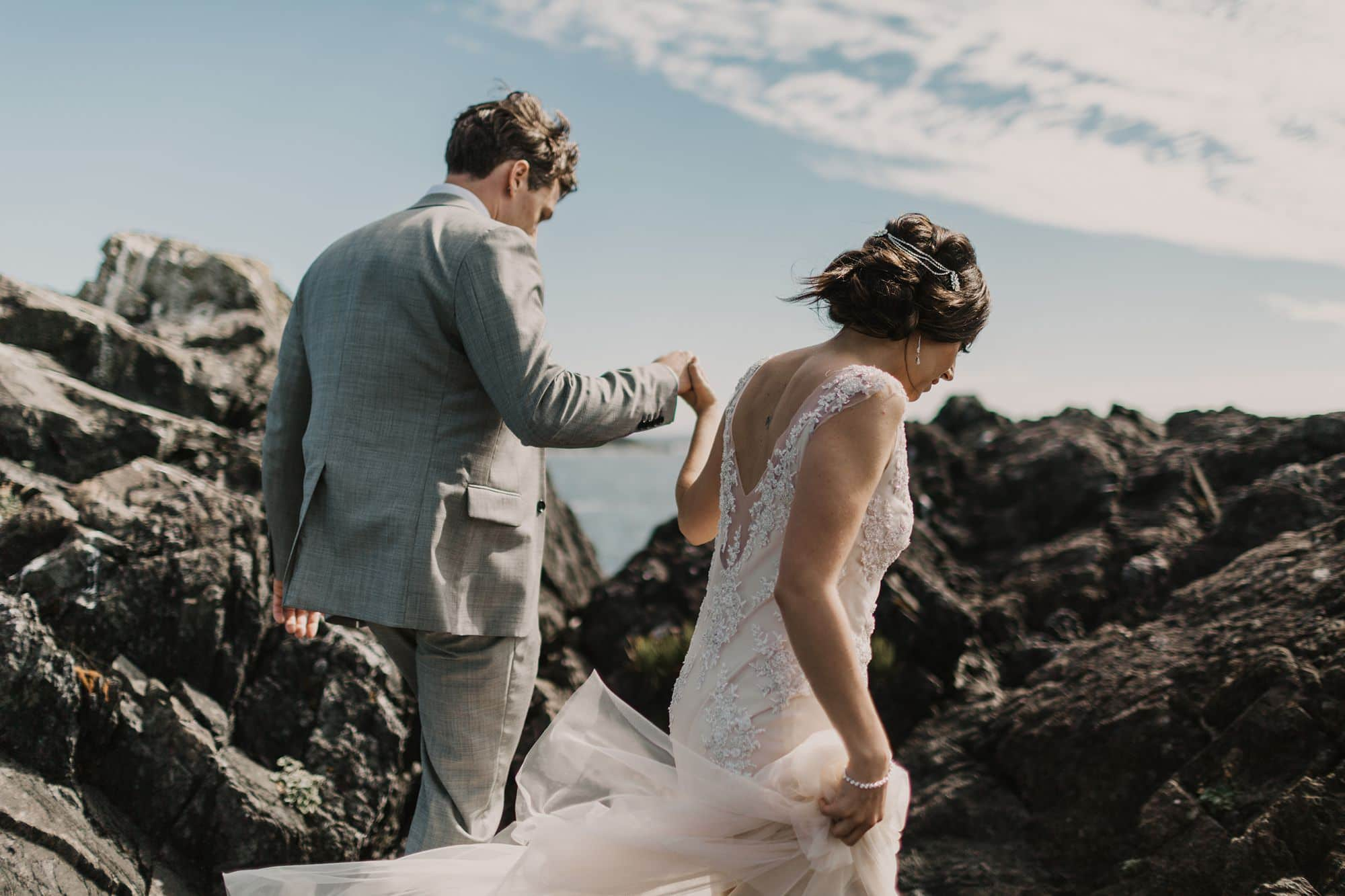 bride and groom walking along rocky cliffs of Tofino