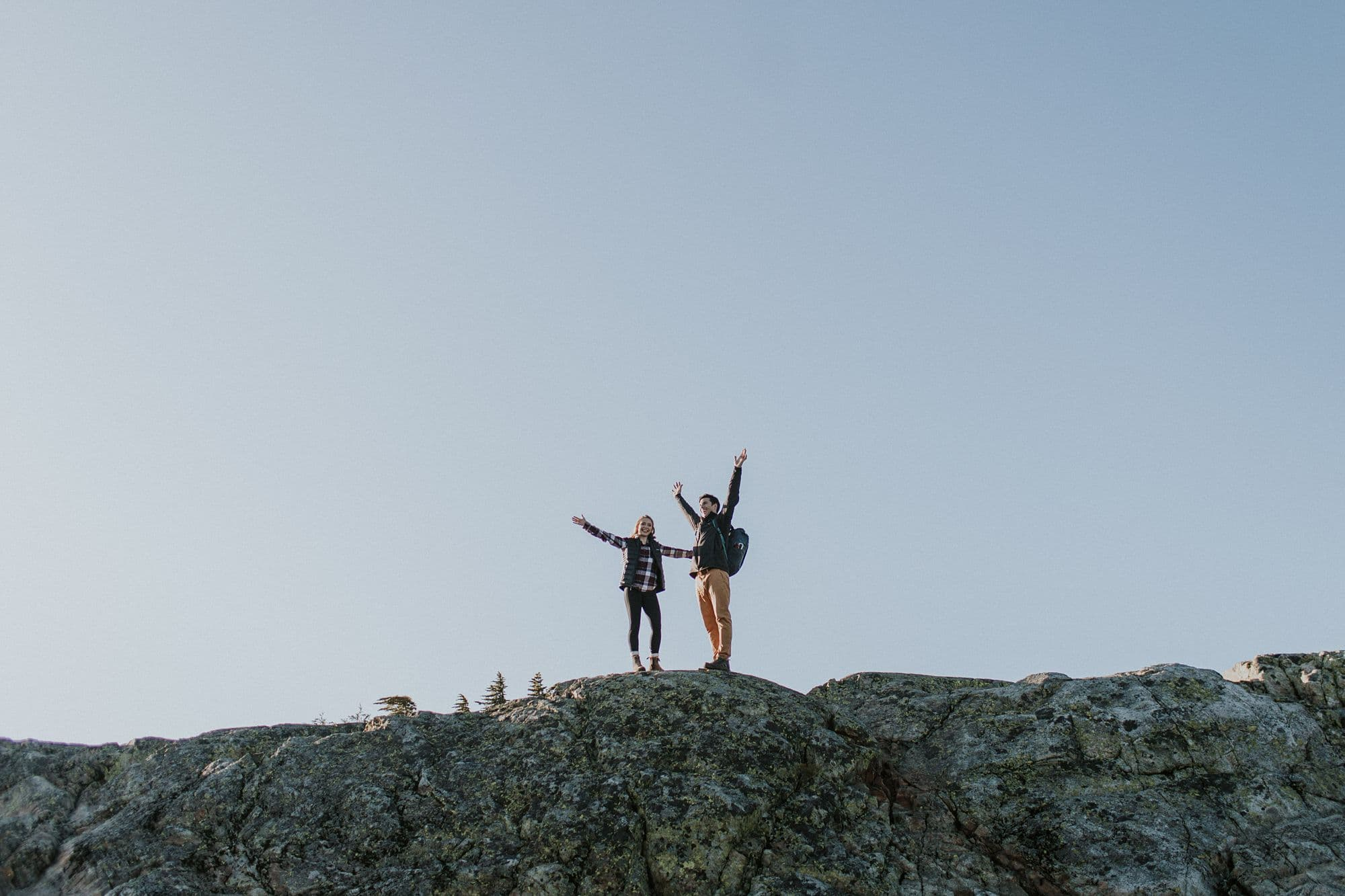 Couple with hands up in the air celebrating the completion of their hike