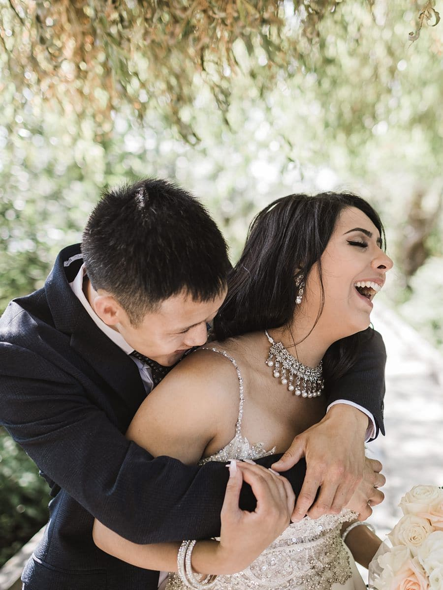 Groom hugging Bride from behind and kissing her shoulder, while Bride is laughing
