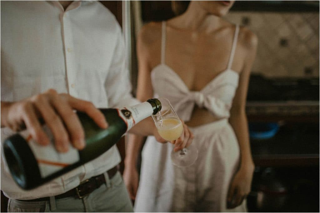 social distancing engagement session - close up of man making a mimosa