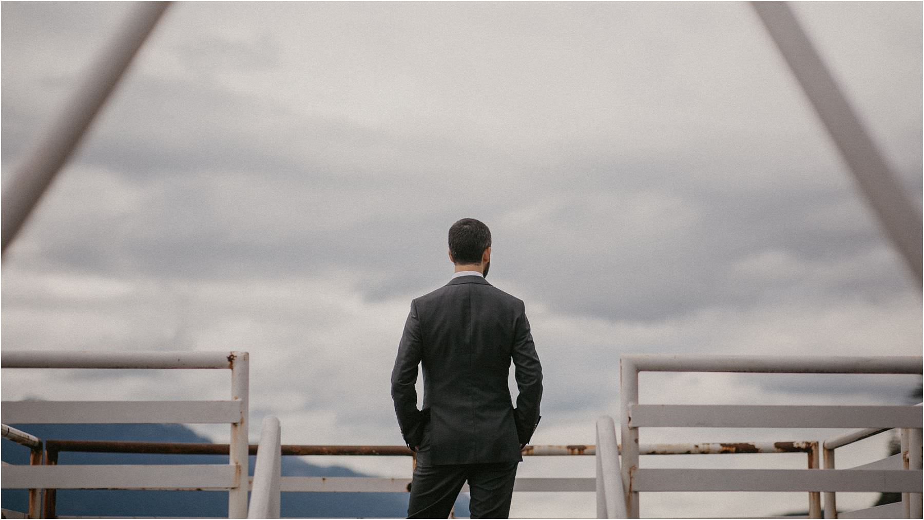Groom standing at the lookout at Porteau Cove waiting for his bride to be before his micro wedding in squamish