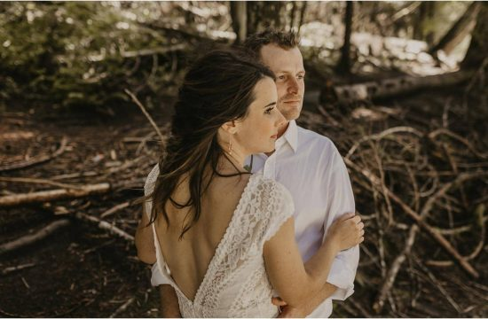 Vancouver Wedding Videographer - Bride and Groom standing in the forest watching the Squamish River flow by.