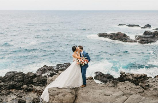 maui dream destination wedding - bride and groom standing on top of a cliff kissing each other