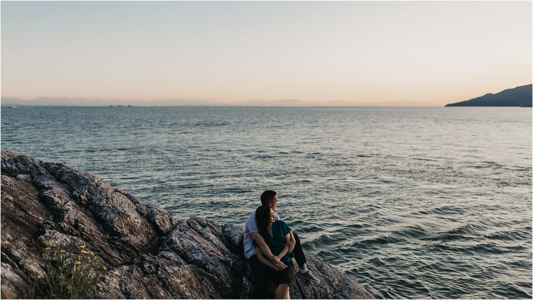 Top 5 Locations for your engagement shoot in vancouver. A couple sit on a rocky shore enjoying the sunset at Lighthouse Park in West Vancouver.