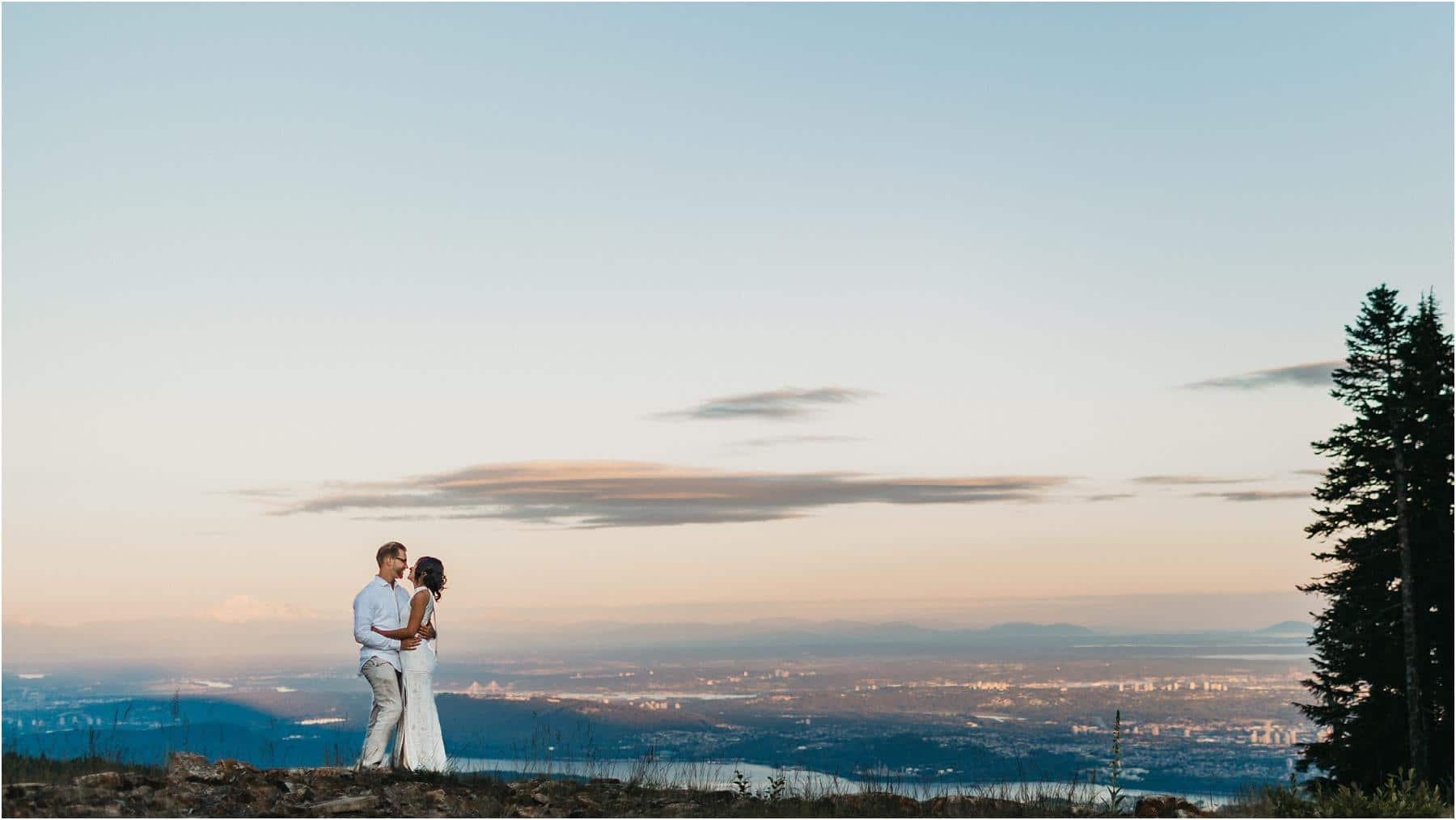 Top 5 Locations for your engagement shoot in vancouver- Couple standing and hugging with the beautiful backdrop of downtown vancouver in the background.