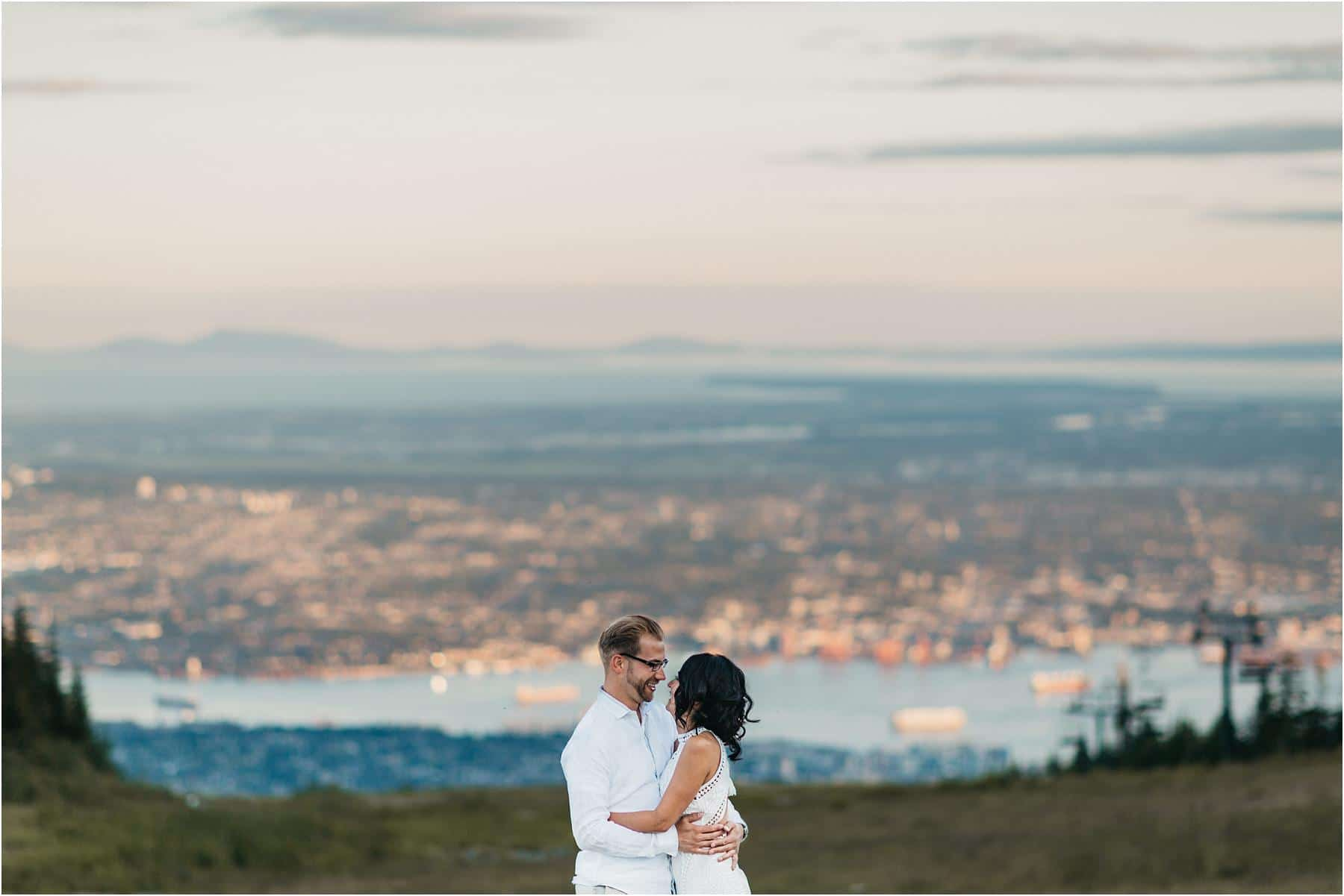 Top 5 Locations for your engagement shoot in vancouver - A couple hugging and smiling at each other with Vancouver cityscape in the backdrop.