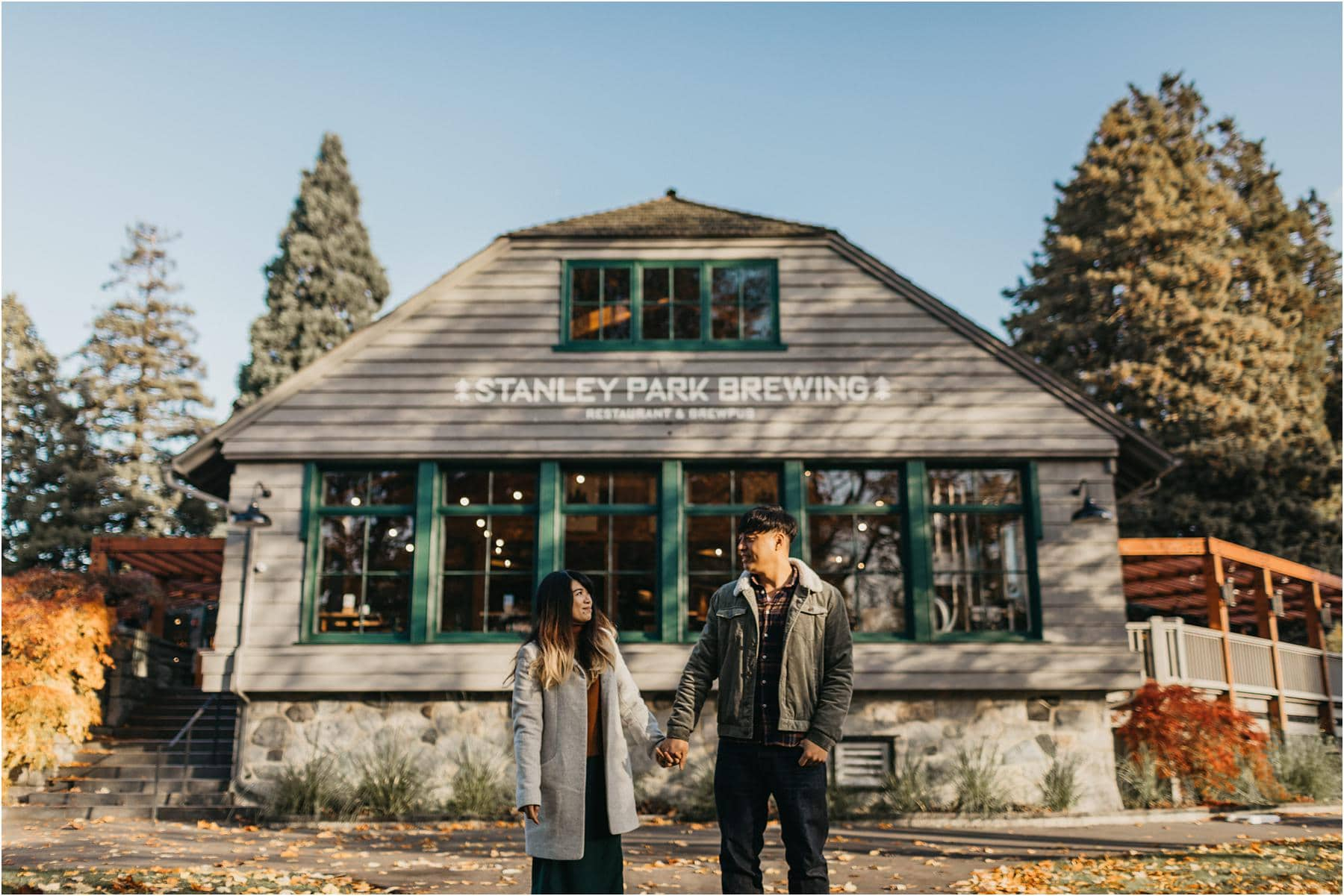 Top 5 Locations for your engagement shoot in vancouver - Couple holding hands and looking at each other while standing in front of Stanley Park Brewing Restaurant
