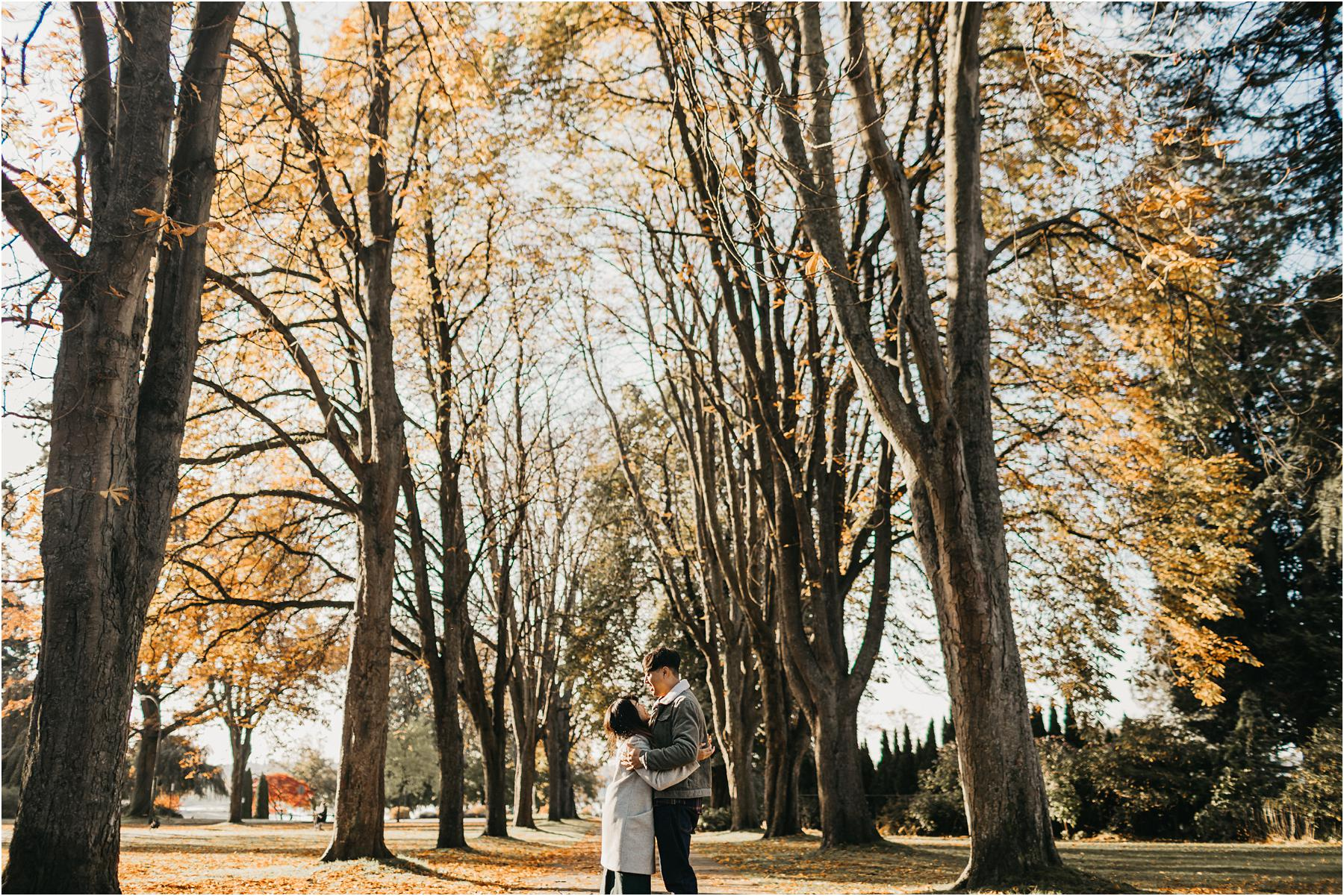 Top 5 Locations for your engagement shoot in vancouver - Couple hugging with fall foliage in background in stanley park