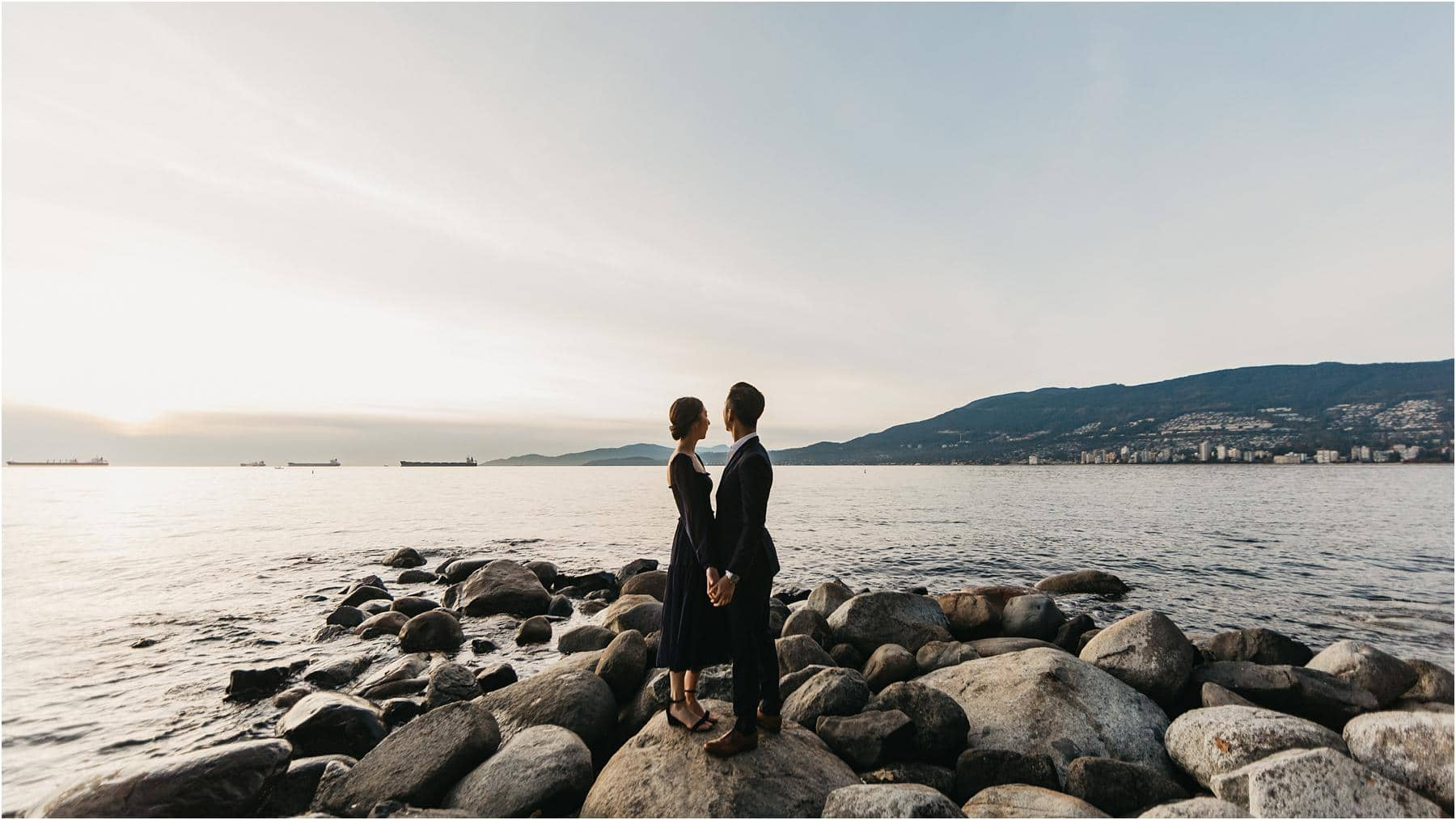 Couple standing on a rocky shore at third beach in stanley park during sunset - Top 5 Locations for your engagement shoot in vancouver