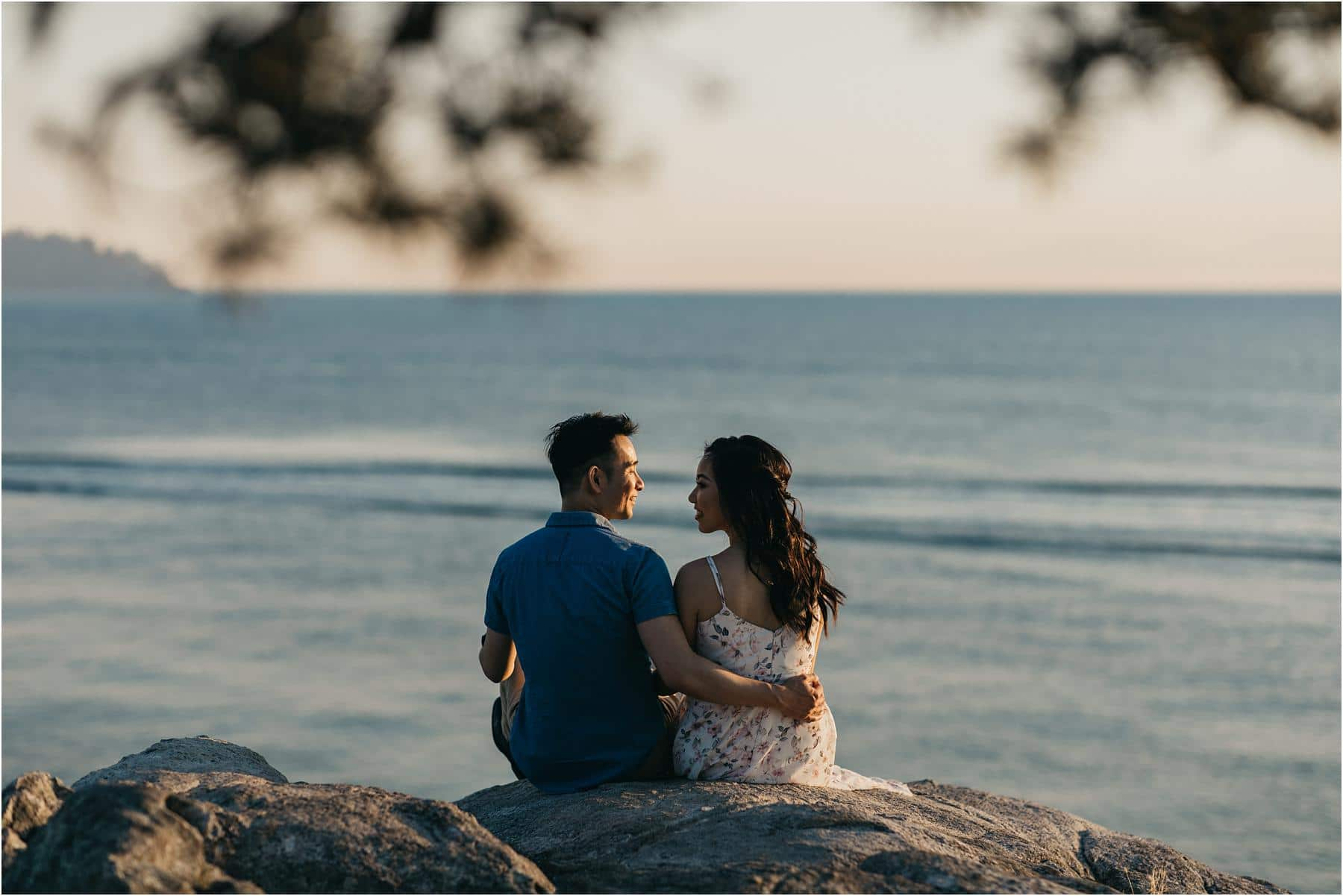 Couple sitting on the edge of a cliff at whytecliff park - Top 5 Locations for your engagement shoot in vancouver