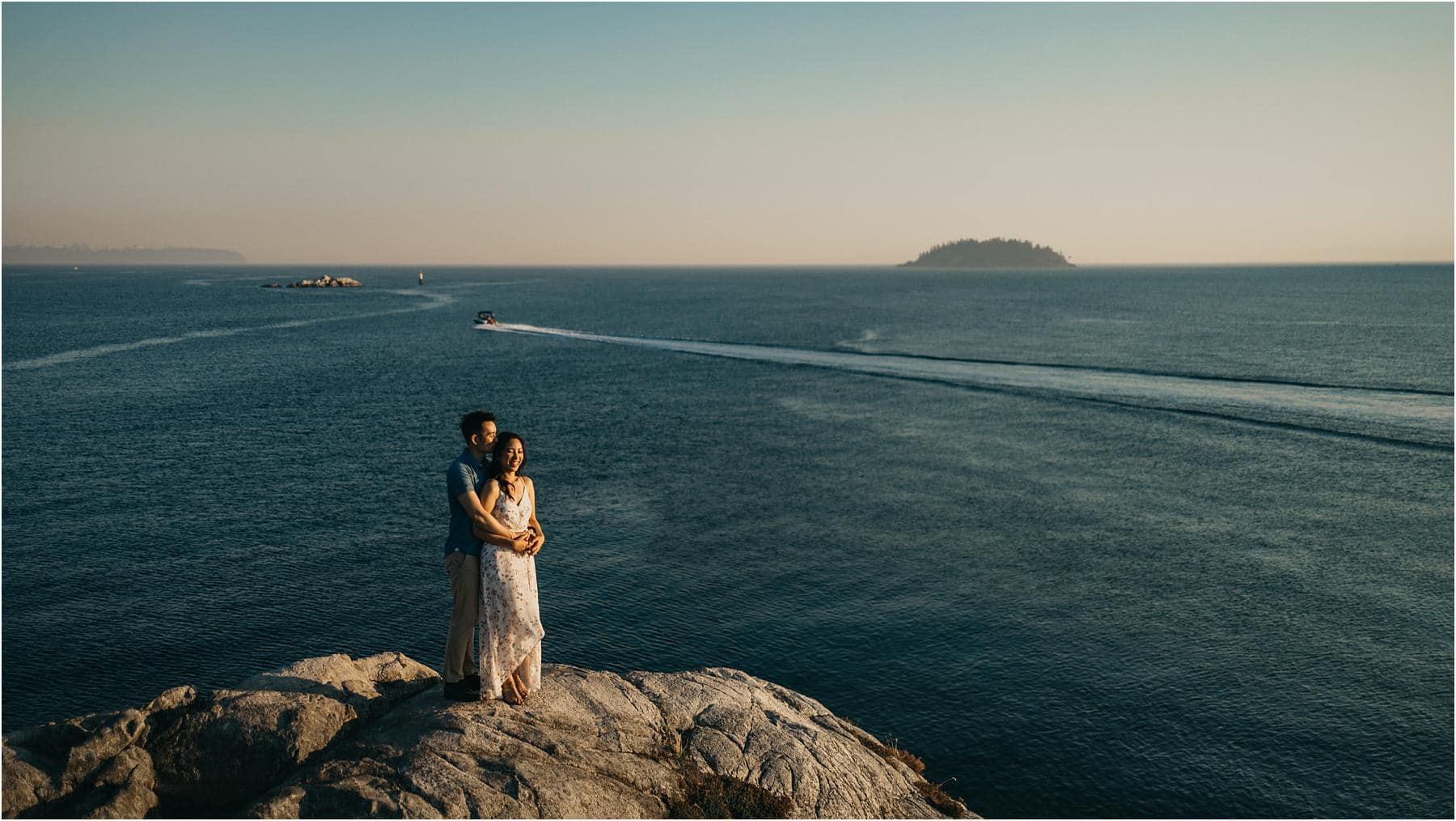 Engaged couple standing at the edge of a cliff and hugging at whytecliff park - Top 5 Locations for your engagement shoot in vancouver