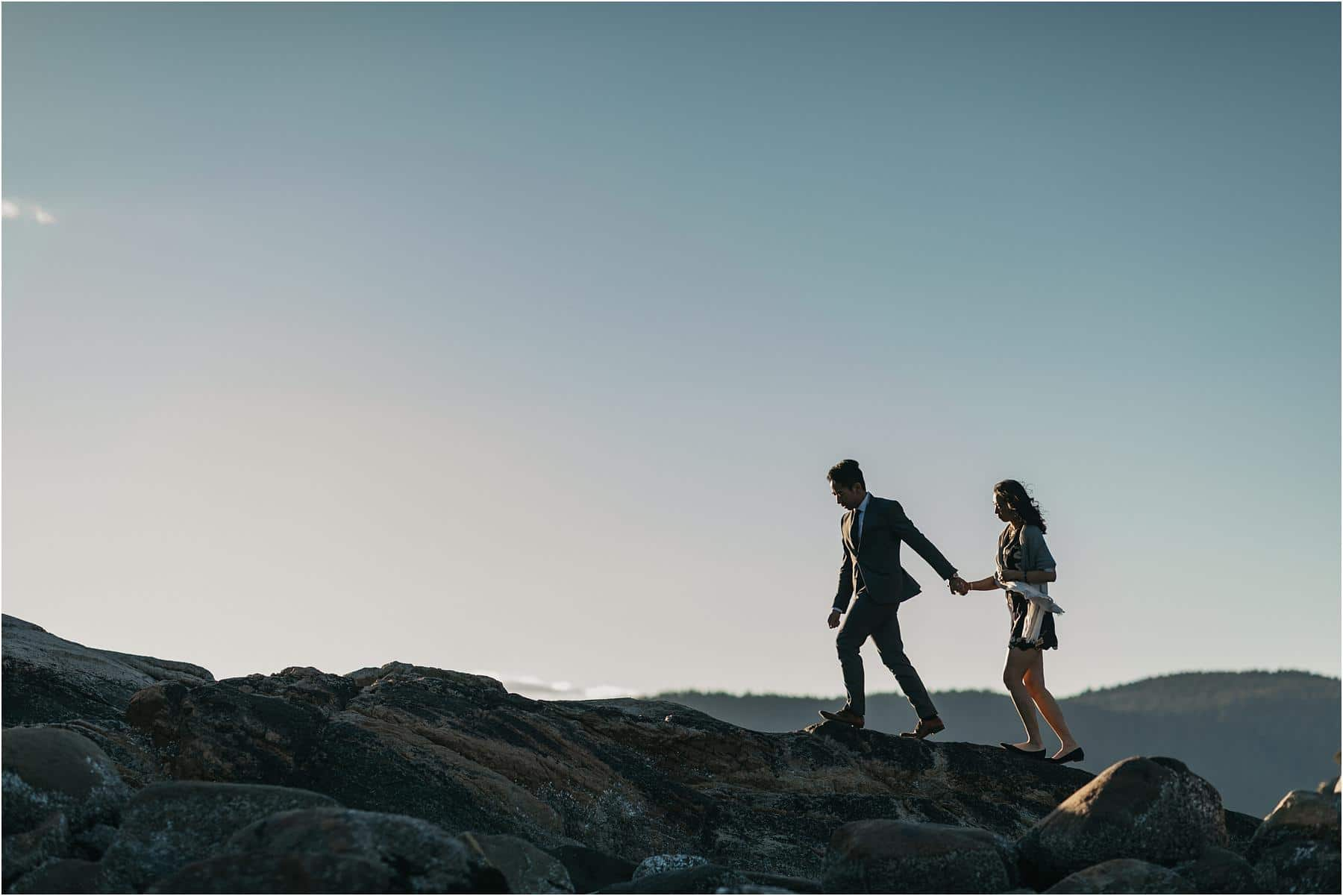 Man leading woman while walking along the cliffs at whytecliff park - Top 5 Locations for your engagement shoot in vancouver