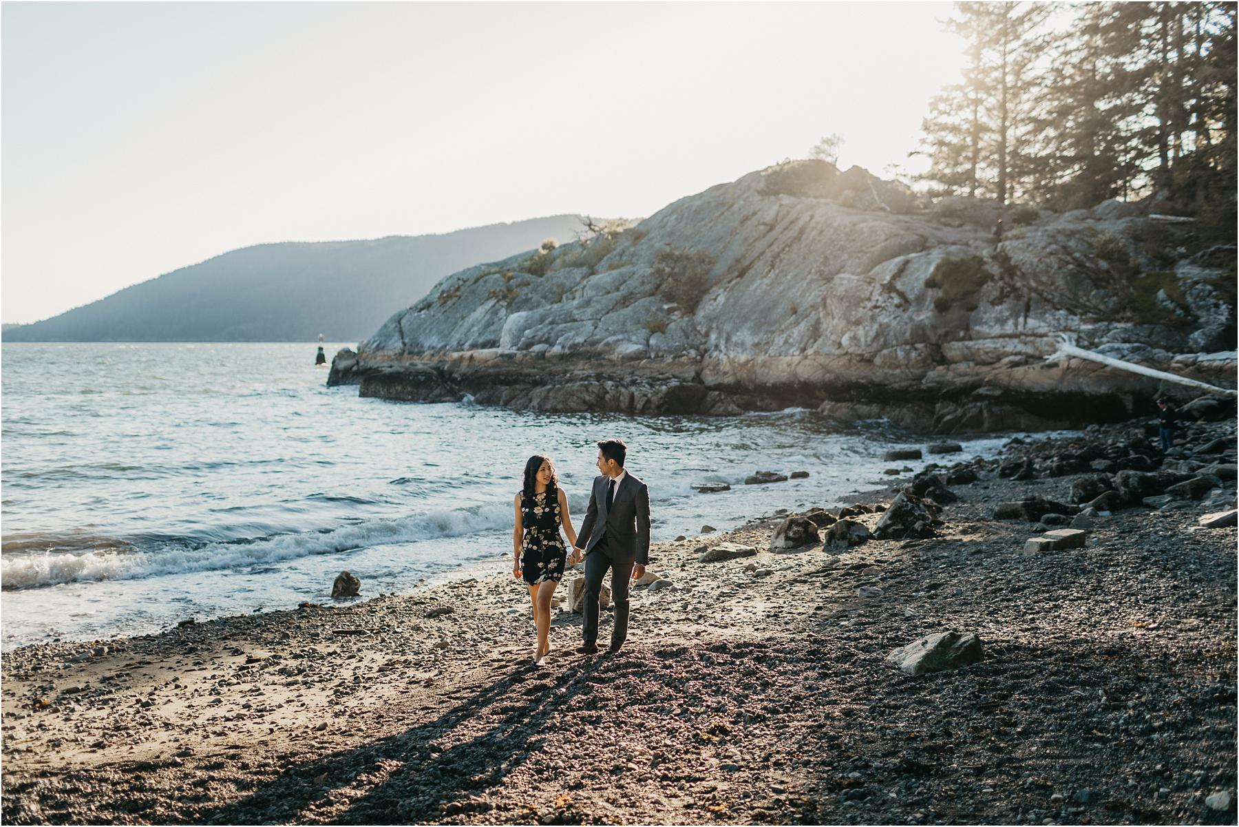 Couple holding hands and walking on the pebble beach at whytecliff park - Top 5 Locations for your engagement shoot in vancouver