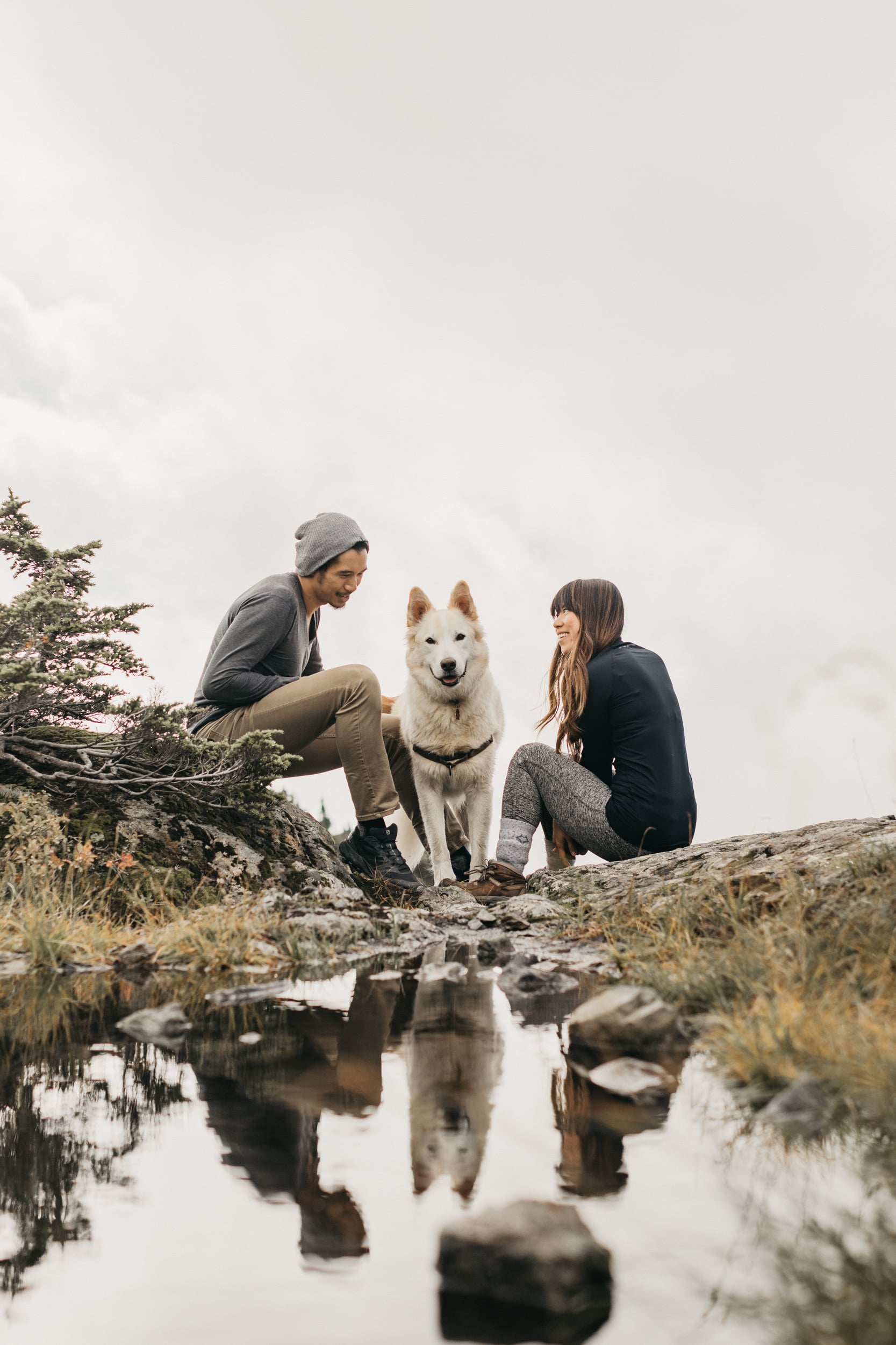 David, Justina and Nazko on top of Mount Seymour with their reflections in a pool of water