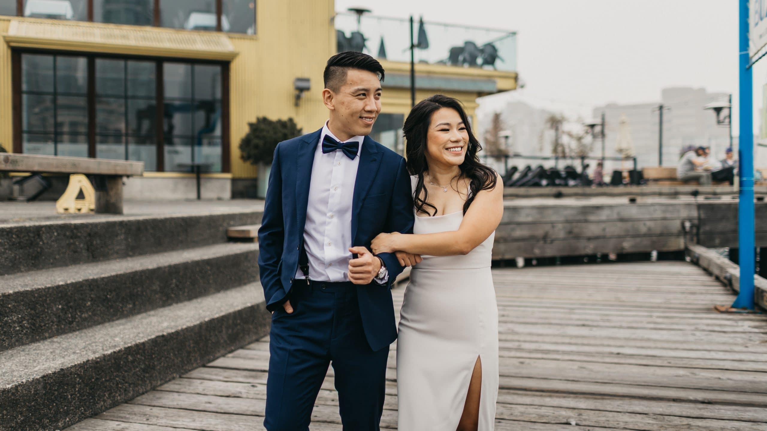 Vancouver Elopement. Young couple walking on a boardwalk on granville island in front of bridges restaurant